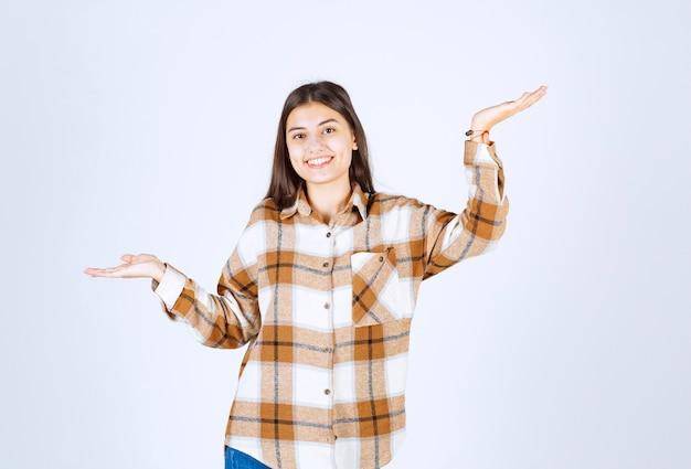 Portret van een jonge vrouw die op de witte muur staat en zich voordeed.