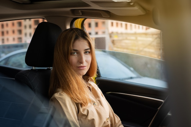 Portret van een jonge vrouw die op een bestuurdersstoel van een auto zit en staart