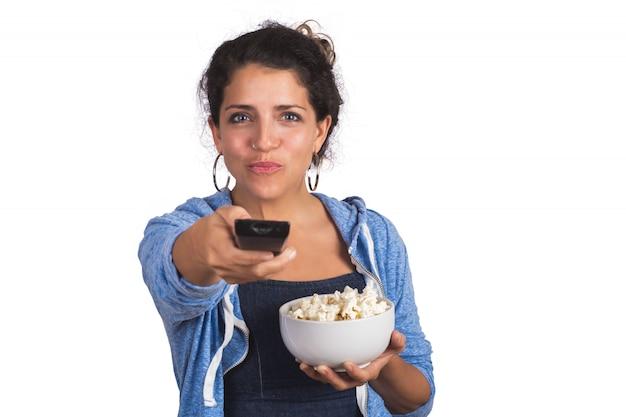 Portret van een jonge vrouw die op een film let en popcorn eet op studio.