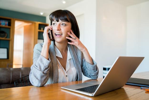Portret van een jonge vrouw die op haar mobiele telefoon praat en thuis werkt met een laptop. kantoor aan huis concept. nieuwe normale levensstijl.