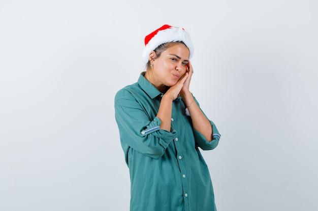 Portret van een jonge vrouw die op handpalmen leunt als kussen in shirt, kerstmuts en er vredig vooraanzicht uitziet Gratis Foto