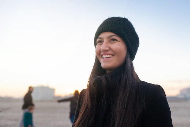Portret van een jonge vrouw die op het strand met winterkleding lacht.