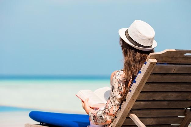 Portret van een jonge vrouw die op het strand ontspant, dat een boek leest