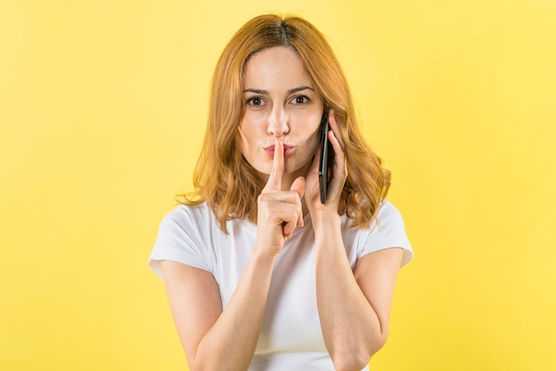 Portret van een jonge vrouw die op mobiele telefoon spreekt die vinger plaatst over lippen die aan camera kijken