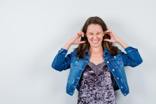 Portret van een jonge vrouw die oren stopt met vingers in een spijkerjasje en er geïrriteerd vooraanzicht uitziet