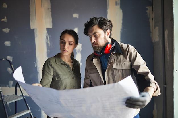 Portret van een jonge vrouw die plattegronden met aannemer bekijkt terwijl status tegen droge muur in in aanbouw huis, exemplaarruimte