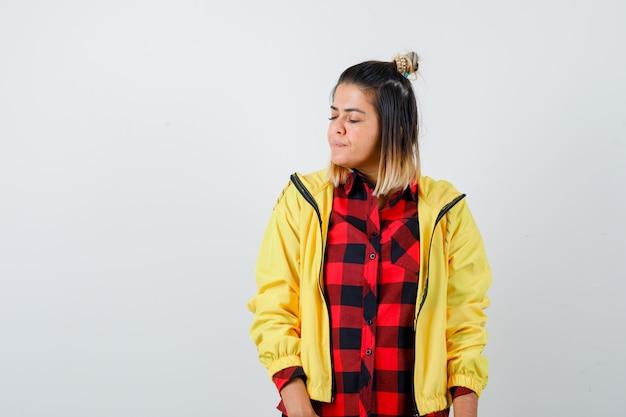 Portret van een jonge vrouw die poseert terwijl ze de ogen sluit in een geruit hemd, een jas en er nieuwsgierig uitziet aan de voorkant Gratis Foto
