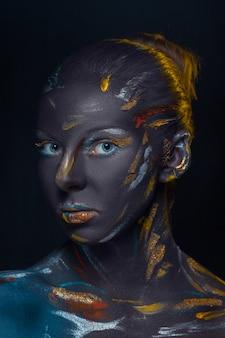 Portret van een jonge vrouw die poseren bedekt met zwarte verf