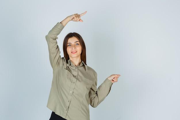Portret van een jonge vrouw die recht in shirt, rok wijst en er vrolijk vooraanzicht uitziet