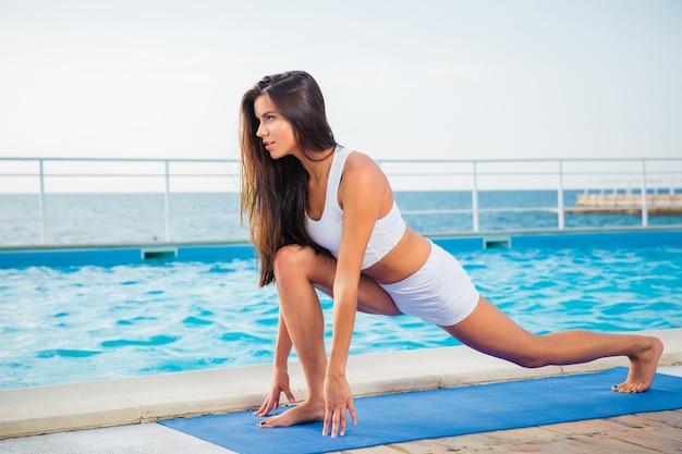 Portret van een jonge vrouw die rekoefeningen op yogamat buiten in de ochtend doet