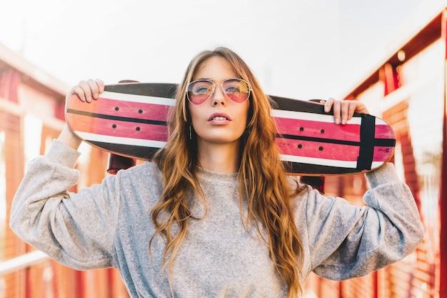 Portret van een jonge vrouw die rode glazen draagt en een lange raadsschaats houdt