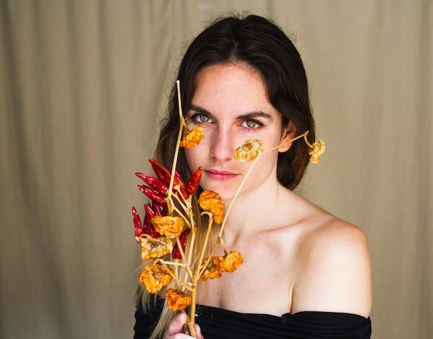 Portret van een jonge vrouw die rode spaanse peperspeper houdt