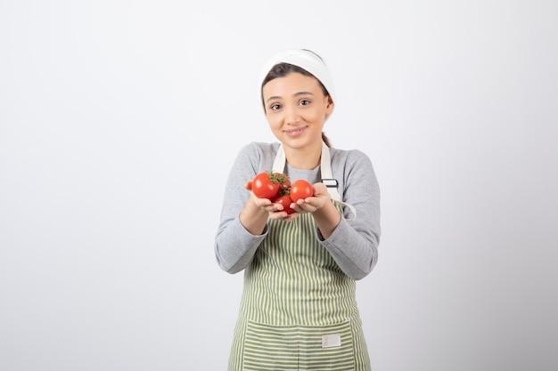 Portret van een jonge vrouw die rode tomaten over witte muur toont