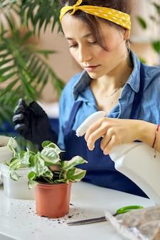 Portret van een jonge vrouw die 's morgens thuis planten sproeit met een spuitfles tijdens het water geven