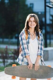 Portret van een jonge vrouw die 's ochtends met een skateboard in een park poseert