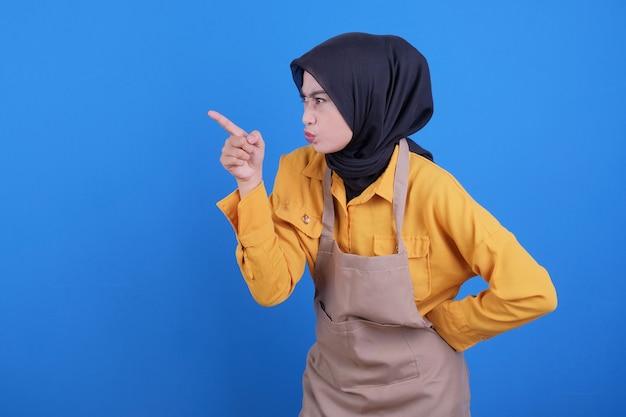 Portret van een jonge vrouw die schort draagt die boos gebaar toont