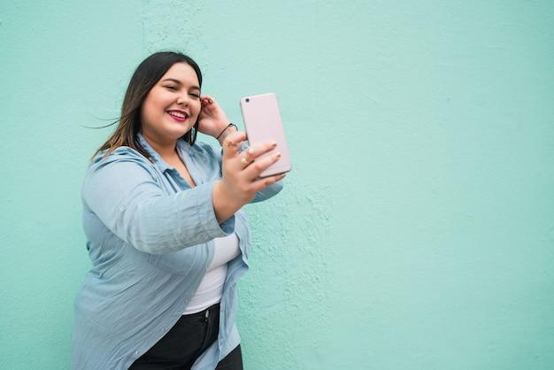 Portret van een jonge vrouw die selfies met haar mophile telefoon buitenshuis neemt