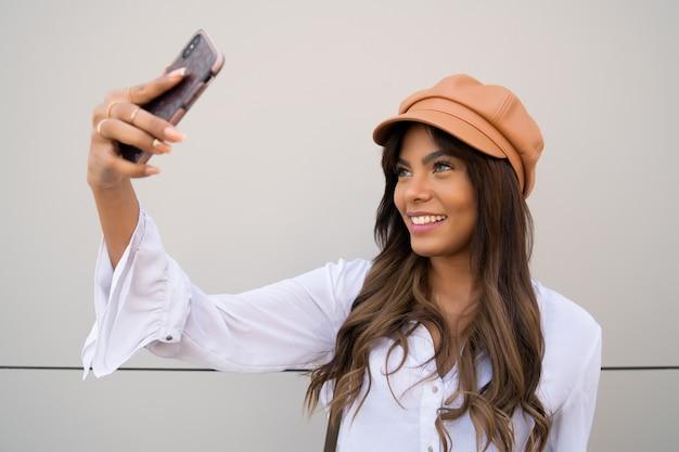 Portret van een jonge vrouw die selfies neemt met haar mophile telefoon terwijl ze buiten staat