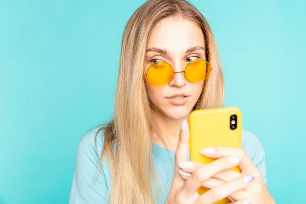 Portret van een jonge vrouw die smartphone gebruikt en geïsoleerd blauw denkt.