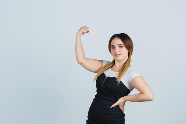 Portret van een jonge vrouw die spieren toont