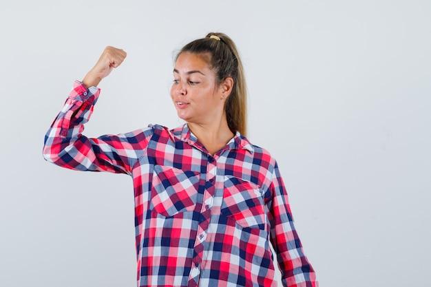 Portret van een jonge vrouw die spieren van de arm in casual shirt toont en zelfverzekerd vooraanzicht kijkt