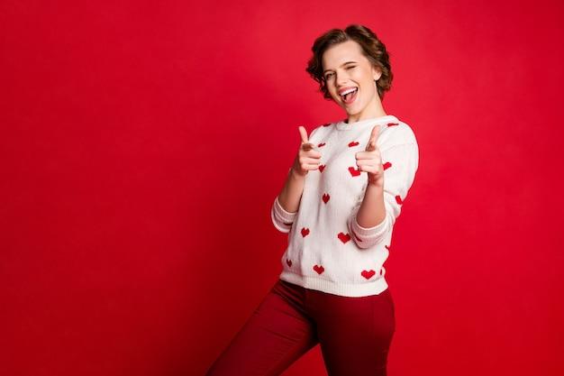 Portret van een jonge vrouw die stijlvolle trendy trui draagt geïsoleerd op rode muur