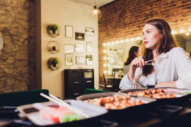 Portret van een jonge vrouw die sushi met eetstokjes eet.