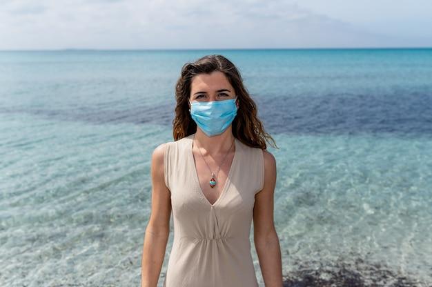 Portret van een jonge vrouw die tegen blauw helder water aan de zee staat en naar de camera kijkt met een chirurgisch beschermend gezichtsmasker.