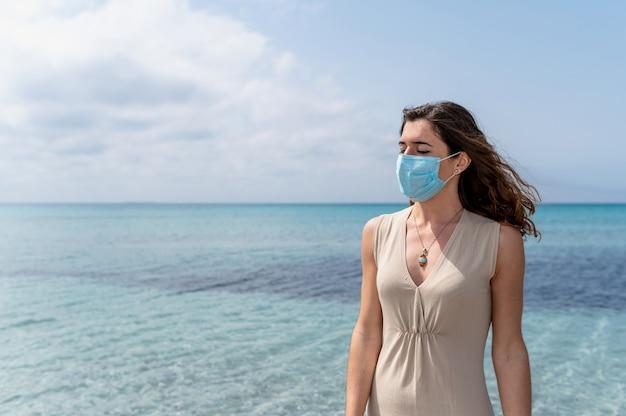 Portret van een jonge vrouw die tegen blauw helder water aan de zee staat en wegkijkt met een chirurgisch beschermend gezichtsmasker