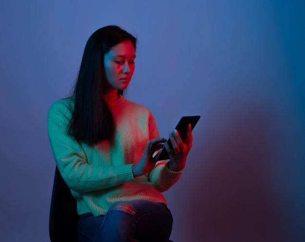 Portret van een jonge vrouw die telefoon op purpere achtergrond met behulp van