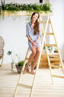 Portret van een jonge vrouw die thuis op de ladder staat of een oranery met groene planten
