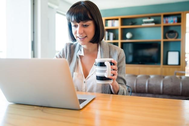 Portret van een jonge vrouw die thuis werkt met een laptop