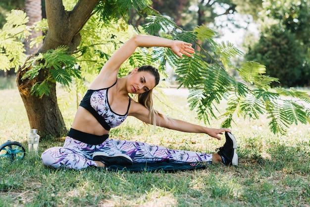 Portret van een jonge vrouw die uitrekkende oefening onder de boom doet