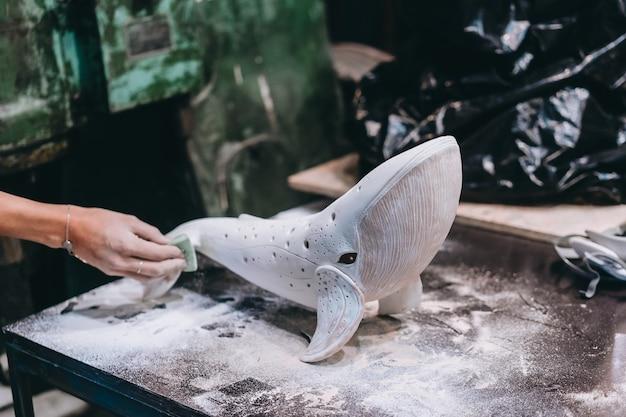 Portret van een jonge vrouw die van favoriete baan in workshop geniet. de pottenbakker werkt zorgvuldig aan de keramische walvis