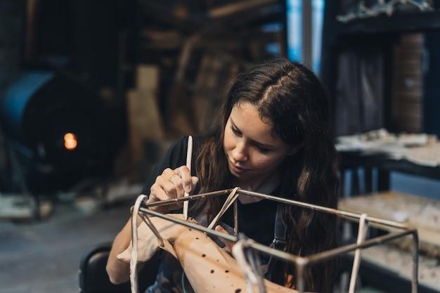 Portret van een jonge vrouw die van favoriete baan in workshop geniet. de pottenbakker werkt zorgvuldig aan de kleiwalvis