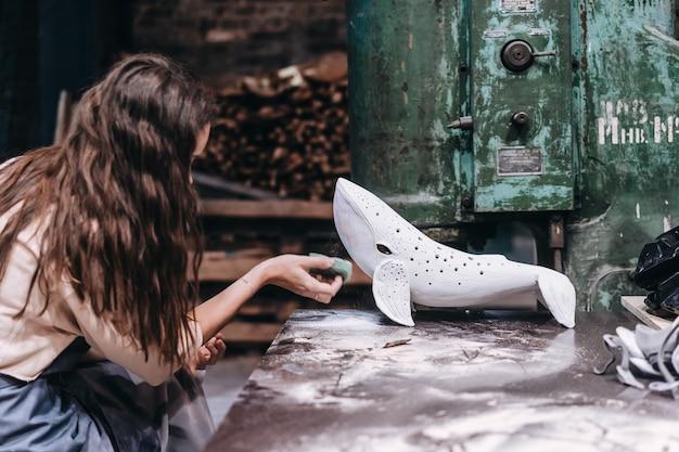 Portret van een jonge vrouw die van favoriete baan in workshop geniet. pottenbakker werkt zorgvuldig aan de keramische walvis