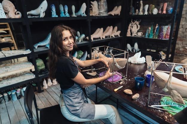 Portret van een jonge vrouw die van favoriete baan in workshop geniet. pottenbakker werkt zorgvuldig aan de kleiwalvis