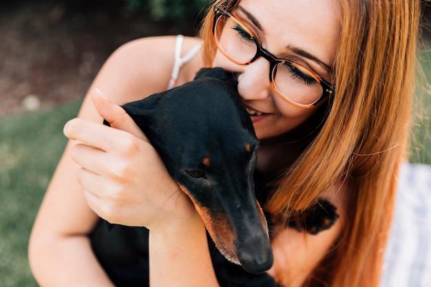 Portret van een jonge vrouw die van haar hond houdt
