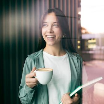 Portret van een jonge vrouw die van koffie geniet