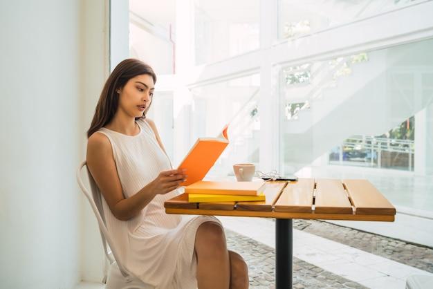 Portret van een jonge vrouw die van vrije tijd geniet en een boek leest terwijl buiten bij coffeeshop zit.
