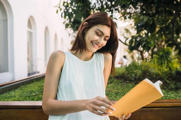 Portret van een jonge vrouw die van vrije tijd geniet en een boek leest terwijl zij buiten zit. levensstijl concept.