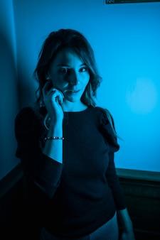 Portret van een jonge vrouw die vanaf de zijkant naar de camera kijkt met blauwe led-verlichting