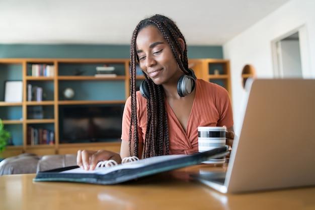 Portret van een jonge vrouw die vanuit huis werkt met laptop en bestanden