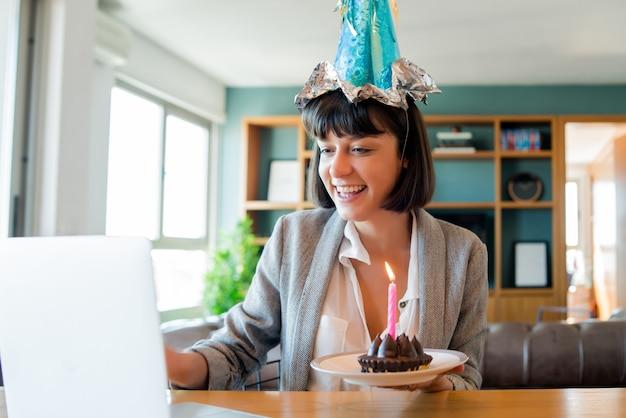 Portret van een jonge vrouw die verjaardag viert tijdens een videogesprek met laptop en cake van huis