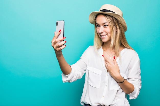 Portret van een jonge vrouw die videogesprek op smartphone maakt, die bij camera zwaait die over blauwe muur wordt geïsoleerd
