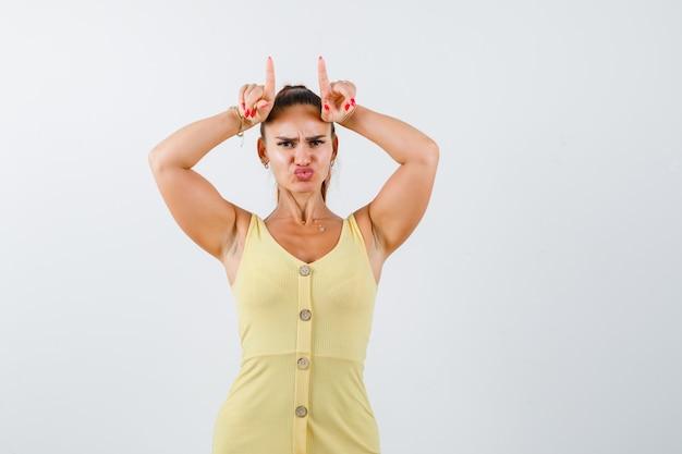 Portret van een jonge vrouw die vingers boven het hoofd houdt als stierhoorns, lippen pruilend terwijl ze fronsend in gele jurk
