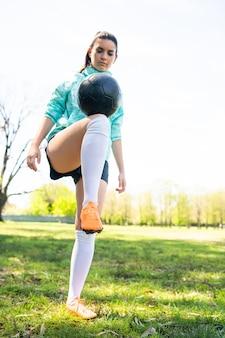 Portret van een jonge vrouw die voetbalvaardigheden oefent en trucs doet met de voetbalbal