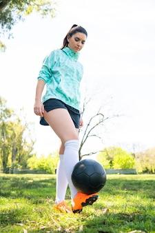 Portret van een jonge vrouw die voetbalvaardigheden oefent en trucs met de voetbalbal doet