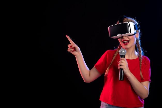 Portret van een jonge vrouw die vr speelt en met microfoon zingt op donkere visuele gamemuziek