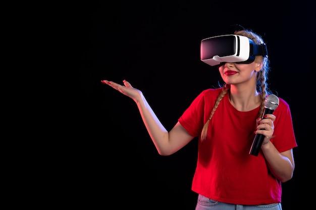 Portret van een jonge vrouw die vr speelt en zingt met een donkere visuele game van de microfoon